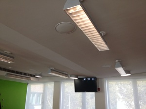 To integrate the central structural beam on one hand, and the side ventilation equipment on the other hand of this large open room, the ceiling is inclined to two converging slopes.
